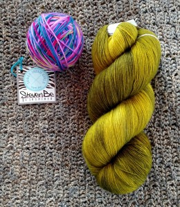 photo of rainbow yarn and a large skein of mossy green yarn